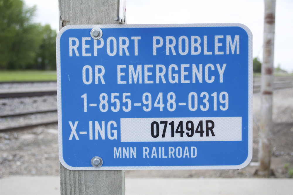 Minnesota Northern RR Emergency Notification System sign attached to wood post.