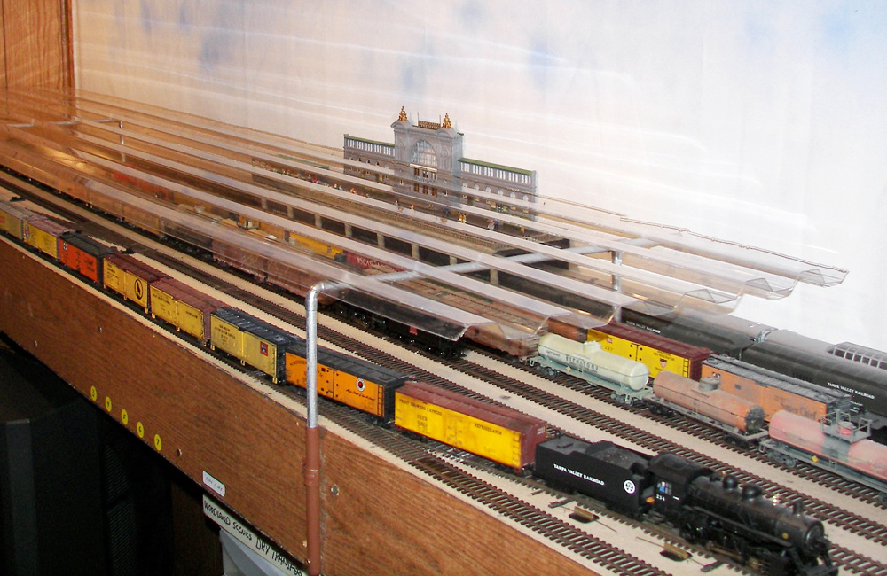 An HO scale train yard on a shelf is covered with a clear corrugated plastic dust cover