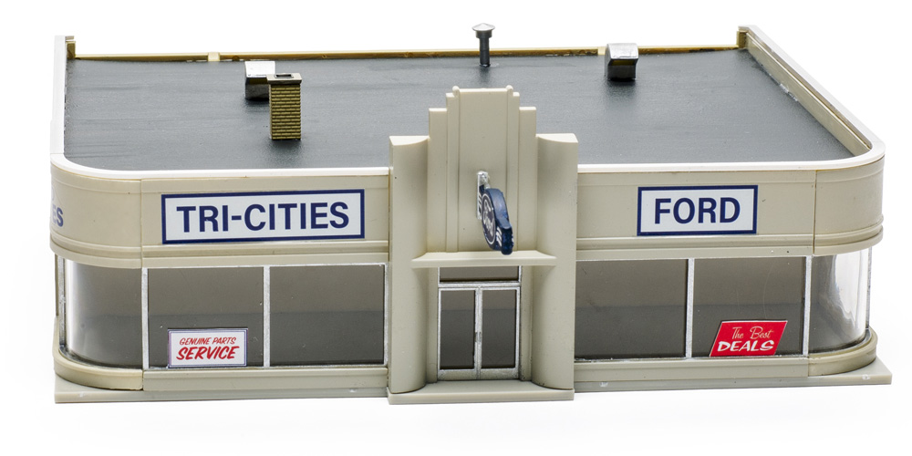 An assembled HO scale kit of an Art Deco-style city auto dealership with large, curved front windows