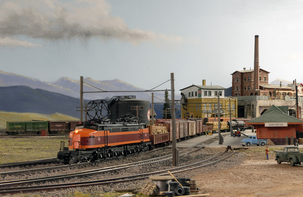 A maroon-and-orange double-ended electric locomotive couples onto a manifest train in front of a depot