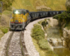 A yellow-and-gray Union Pacific SD7 diesel runs downgrade with a coal train along a racing creek