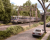 A silver two-car electric SEPTA commuter train glides under an overpass by a residential street