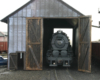 The nose of a steam locomotive is seen through the door of a single-stall wooden engine house