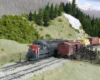 A gray-and-scarlet diesel with a manifest train passes by a stock pen in the mountains