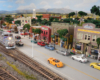 A pair of modern diesels rolls a freight train past a bustling downtown scene
