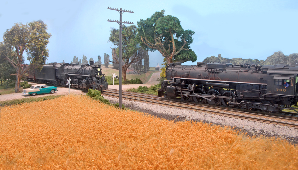 Two HO scale Nickel Plate Road steam locomotives meet at a rural grade crossing on Tony Koester's HO scale model railroad.