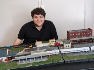 Matthew Mendolia sits posed behind his finished layout