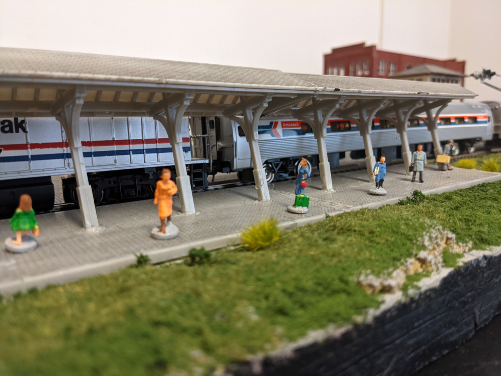 Model figures idling on a station platform with an Amtrak train pulled up