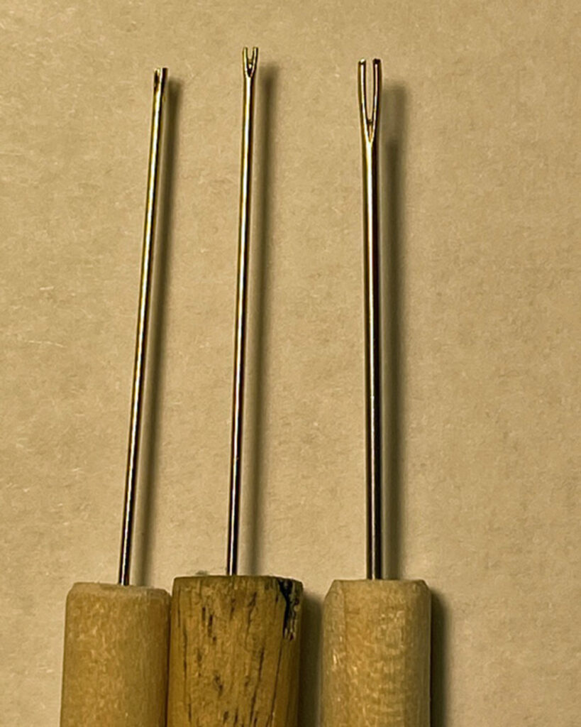 Three sewing needles with their eyes snipped across, inserted in dowel handles