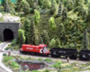 A red-and-black Canadian Pacific diesel switcher pulls a pair of empty hoppers in a wooded setting