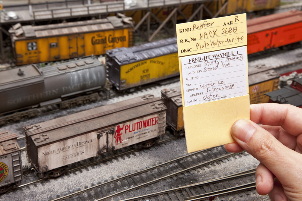 A hand holds up a car card for a refrigerator car, with a destination card in its pocket, in front of the car on an HO scale layout