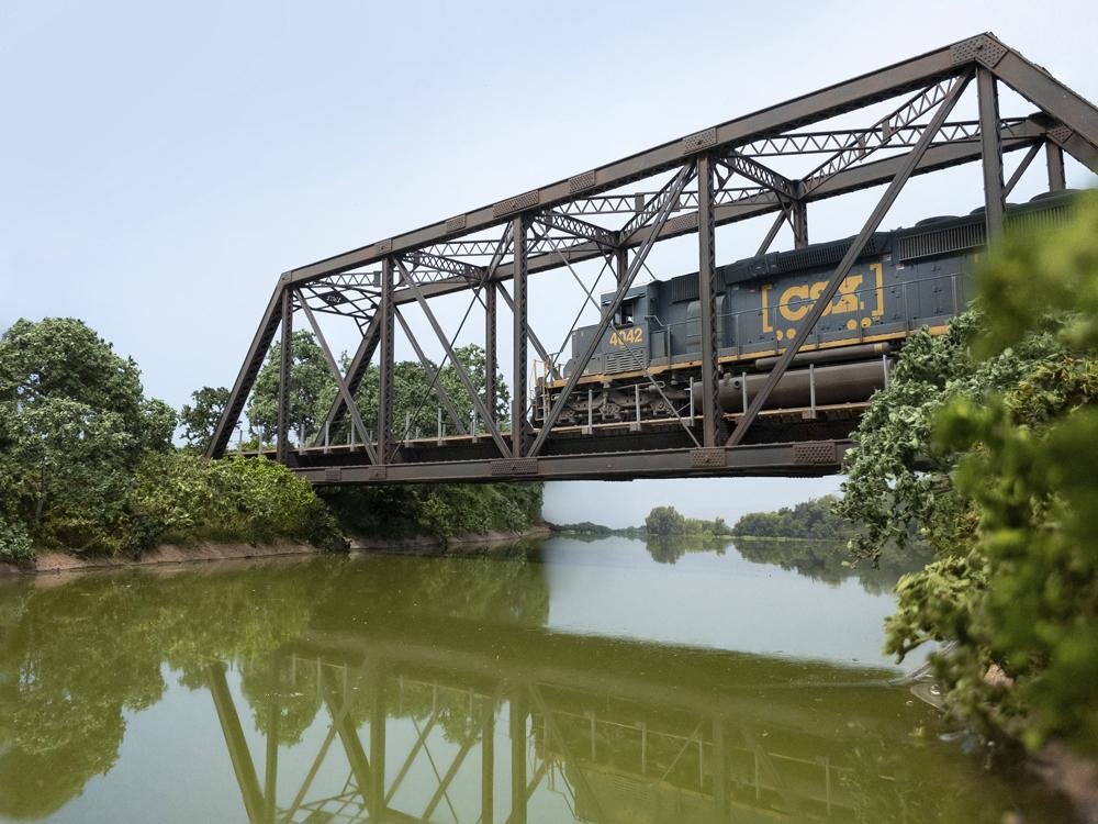 A blue CSX diesel locomotive crosses a truss bridge over a muddy green river