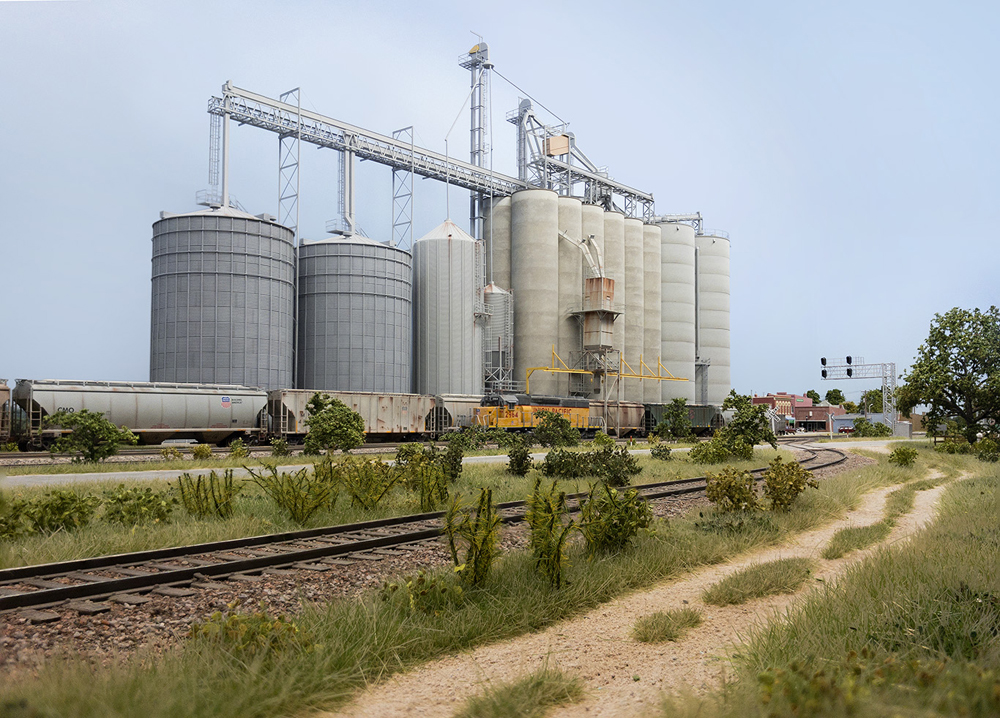 The concrete and corrugated metal silos of a large grain complex dwarf passing trains