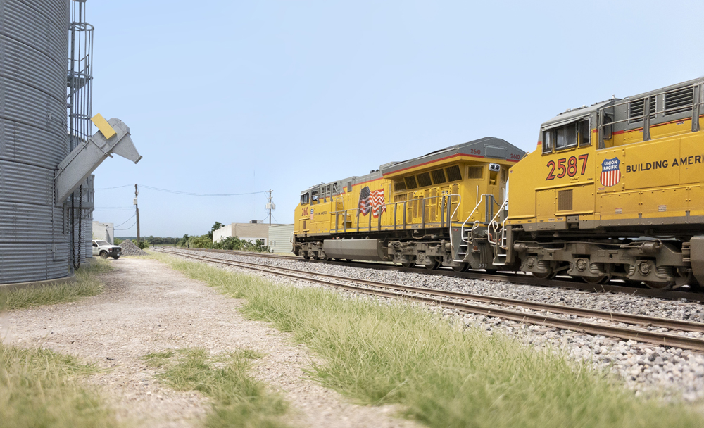 A pair of yellow Union Pacific diesels are seen in low angle in a rural scene