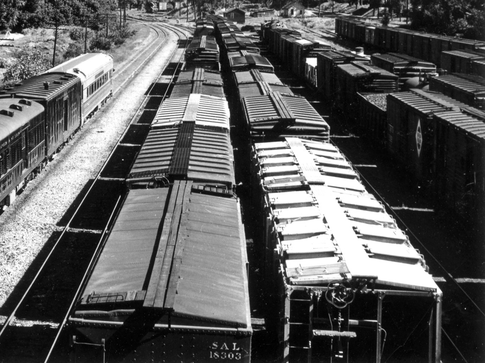 The roofs of several freight cars are seen in a black-and-white photo of a rail yard