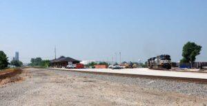 Freight train curves through town behind depot