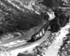 Diesel locomotives with coal train along river in canyon