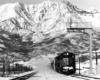 Freight train kicking up snow under a signal gantry
