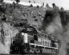 Black smoke follows diesel locomotives exiting tunnel