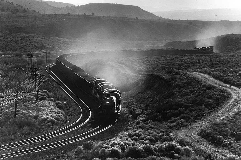 Sun highlight diesel locomotive exhaust of train in curve