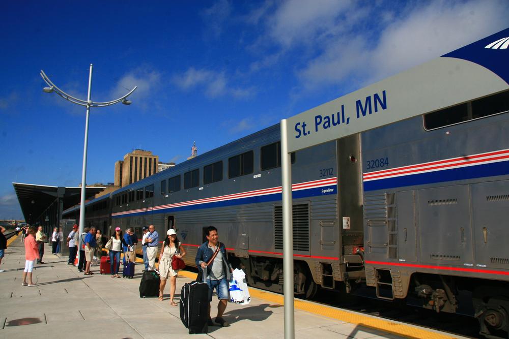 People walk on platform in front of bilevel passenger cars