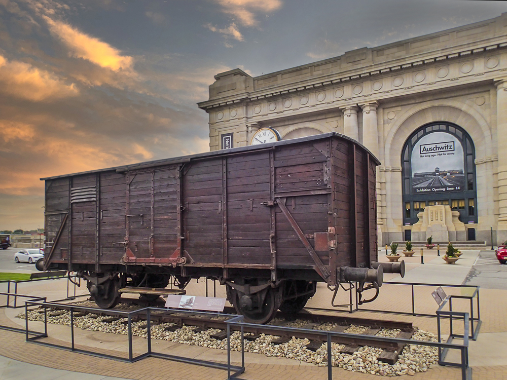 Four-wheeled European freight car on short piece of track outside railroad station