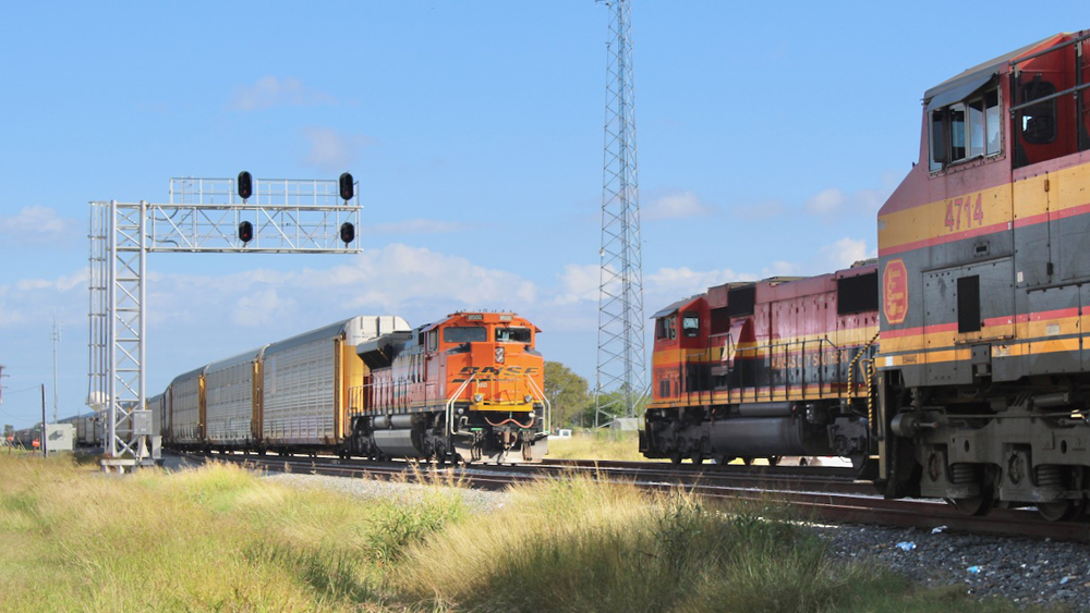 Train with BNSF locomotive passes Kansas City Southern engines