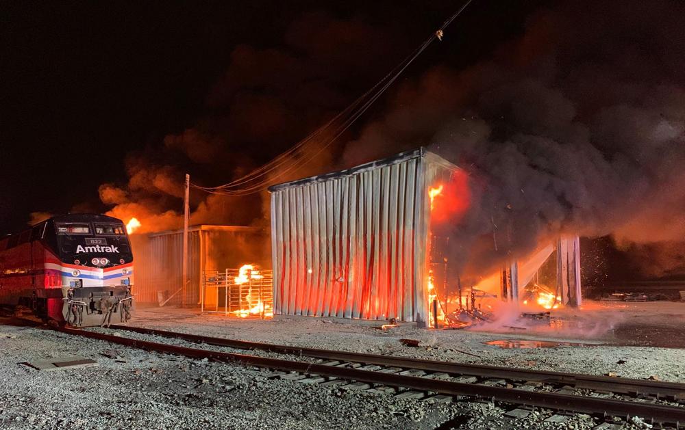 Buildings on fire next to Amtrak locomotive