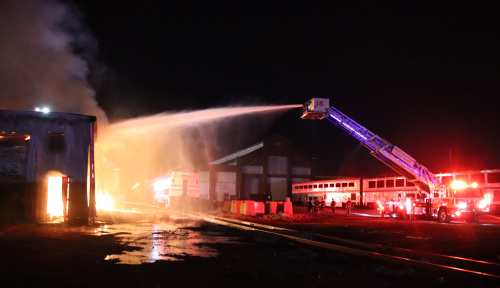 Fire truck spraying water on burning building with passenger cars in background