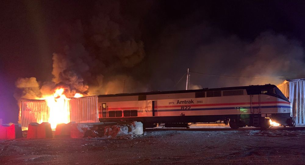 Amtrak locomotive with burning building in background