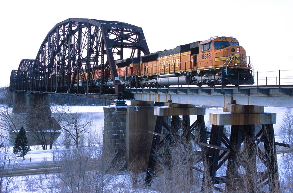 BNSF train crossing river bridge in winter