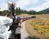 People take pictures in open-air car as train rounds curve
