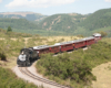 Train negotiates curve with mountains as backdrop