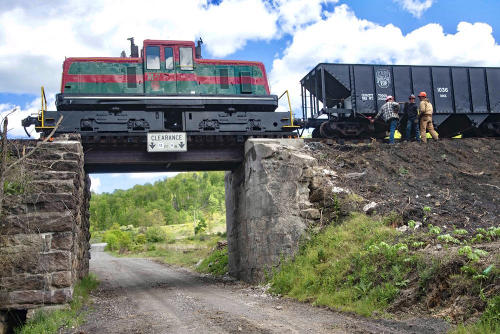 Diesel lcomotive with ballast cars on small bridge