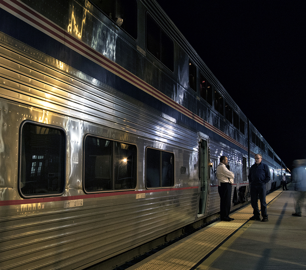 Two men speaking on a station platform in front of a passenger car.