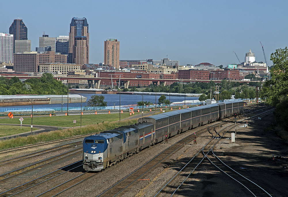 Passenger train running along flat land. A river and big-city skyline are in the middle and backgrounds.