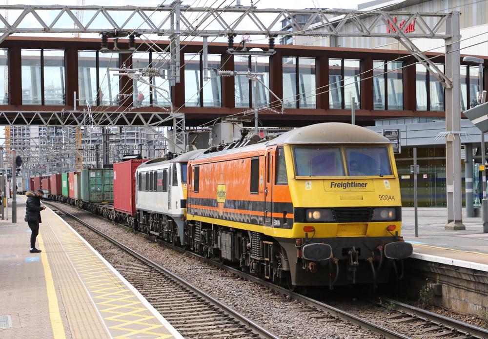 Orange and yllow locomotive leads freight train through passenger station