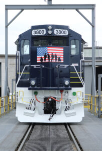 Front view of red, white, and dark blue locomotive