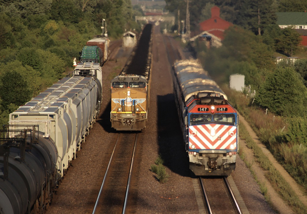 Container train with yellow locomotives approaches on the middle of three tracks.