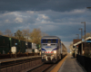 Train with blue and silver locomotive at station platform under billowing clouds.