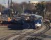 Amtrak passenger train passes Metra commuter train in view from bridge across tracks.