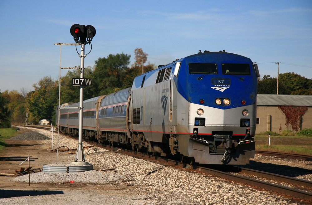 Short passenger train with blue and silver locomotive passes signal