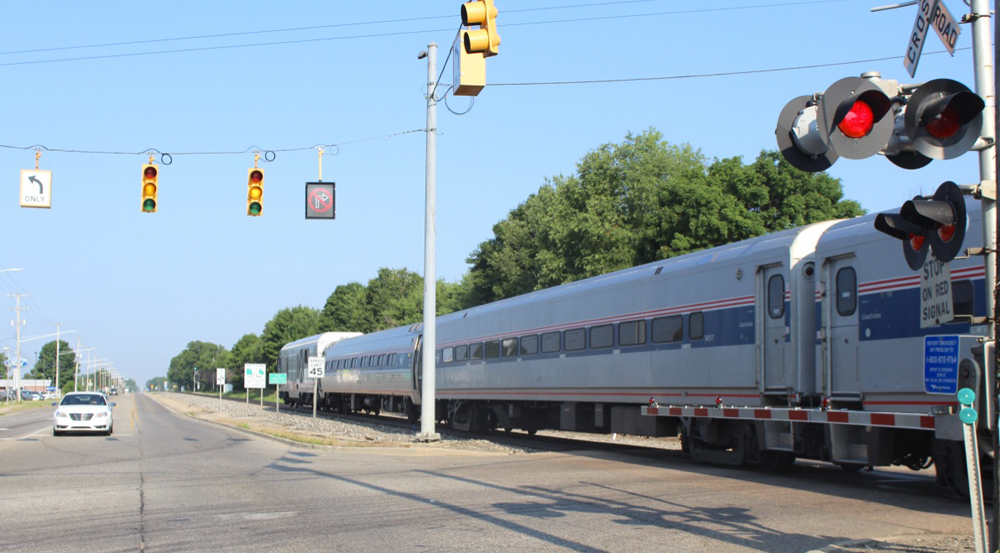 Passenger train paralleling highway passes grade crossingWolverine No. 351 heads toward Kalamazoo and Chicago on July 7, 2020, west of Galesburg, Mich., on another 110 mph. portion of the Chicago-Detroit route