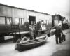 Two men stand on a train platform with a canoe