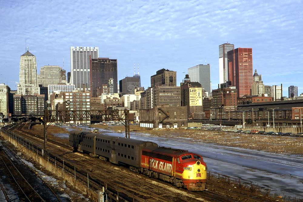 Red and yellow commuter train under Chicago skyline