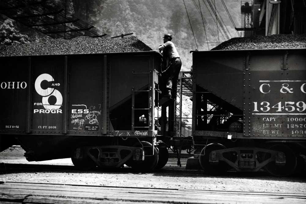 Man climbing between two coal hopper cars