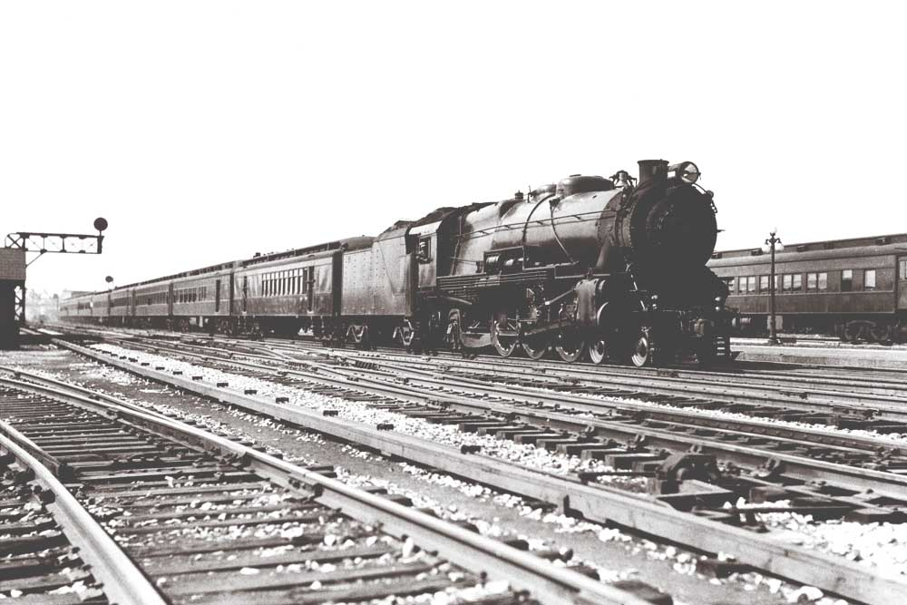 Steam locomotive with passenger train by signal gantry