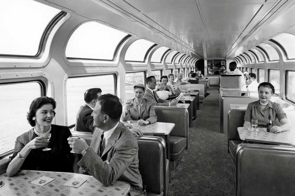Passengers enjoy drinks in a railroad lounge car