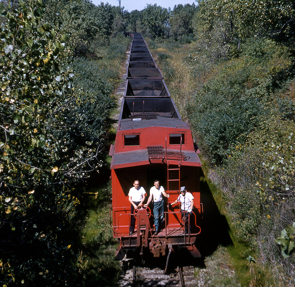 Railroaders on the rear platform of a red caboose behind a long train. Color photograph.