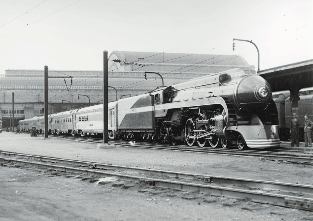 Streamlined steam locomotive with passenger train at station